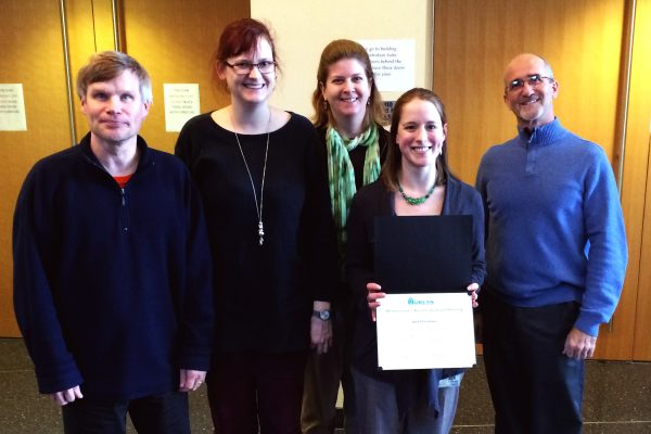 5 people pose together, all smiling. One person holds a Delta certificate in front of her.