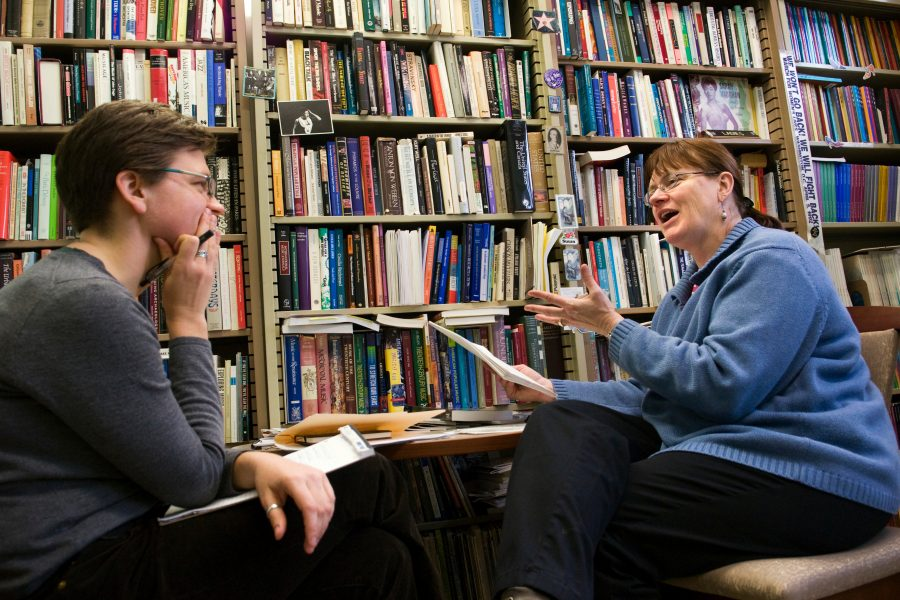 Two people sit facing each other in conversation in an office setting, with a set of bookshelves in the background. The speaker leans in to the listener, hands raised in a gesture, while the listener lightly rests a chin in one hand looking attentive and engaged. Link goes to page of what we offer.