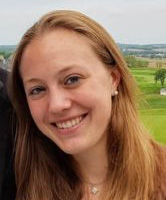 Smiling headshot of a woman with a landscape in the background.