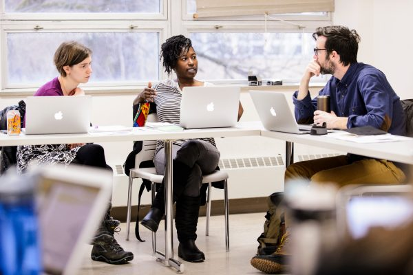 3 people sit and converse around a table, laptops open in front of them, in a classroom setting.