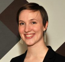Headshot of woman with short hair, smiling at the camera. Link goes to alumni spotlights.