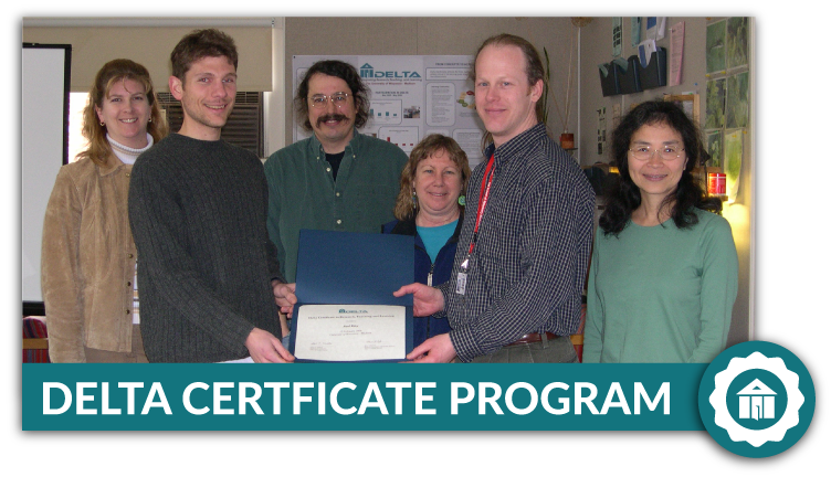 Delta participant proudly receiving the Delta Certificate, surrounded by faculty and Delta staff.